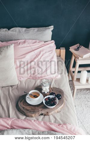 Black loft bedroom and pastel bedding set. Unmade bed with breakfast and reading on tray. Interior decor over blackboard wall. Cozy modern living space.