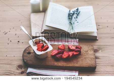 Summer weekend concept. Reading novel and relaxing. Opened book, lavender and yogurt with strawberry on old wooden table.