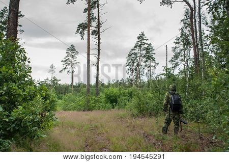photographer-naturalist, a man in camouflage clothes with a backpack, a photographer in the forest