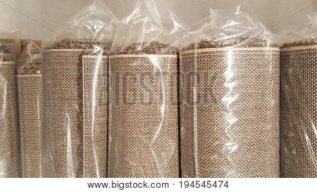 Top view of brown fabric roll wrapped in plastic roll bag / stock of brown fabric for fashion design business, raw material in garment manufacturing