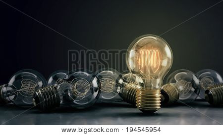 Multiple incandescent light bulbs on a reflective surface and dark background. One hero bulb illuminated standing out from the rest. Great for conveying a big idea or unique business thoughts. 3D illustration.