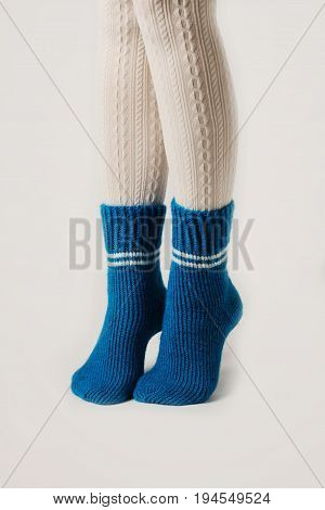 Female legs in white stockings and blue knitted socks.