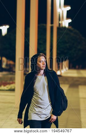 Young handsome casual student in hood outdoors. Portrait of hooded guy walking through night city