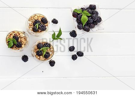 Blackberry parfaits made with Greek yogurt granola and fresh blackberries shot from overhead over white wood table. Room for copy space.