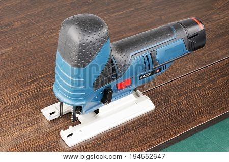 Electrical fretsaw isometric view on brown wooden surface