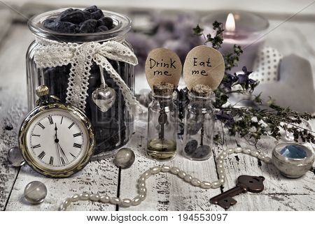 Toned still life with tiny bottles with labels eat me and drink me, old clocks, key and honey berry in vintage jar. Alice in Wonderland background, fairy tale abstract concept with summer flowers