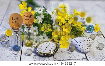 Vintage pocket clocks, tiny bottles with tags drink me, eat me, and crystal balls on planks. Alice in Wonderland background, fairy tale abstract concept with summer flowers