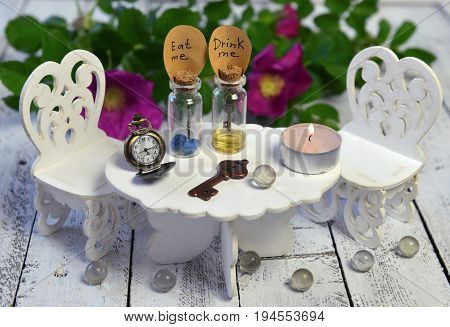 Tiny table with chairs and two bottles with tags eat me, drink me. Alice in Wonderland background, fairy tale abstract concept with summer flowers