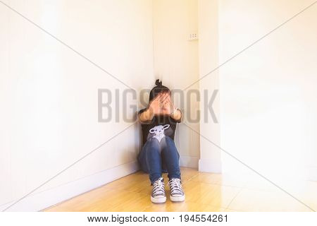 Woman sitting strain unhappy In the corner bow the knee In the corner of the room even when the light shines,blur