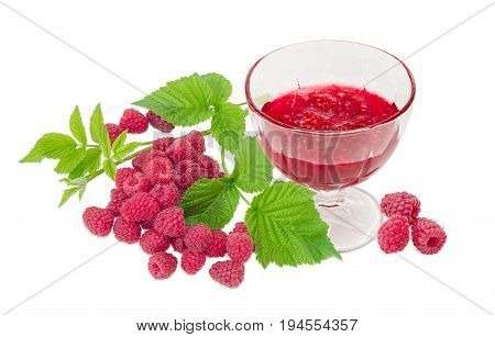 Raspberry jam in the glass dessert stem bowl against of the fresh cultivated red raspberries and raspberry branch with leaves on a light background