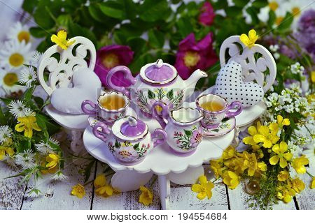 Mad tea party concept with decorated small furniture, cups, teapot and flowers on planks. Alice in Wonderland background, fairy tale abstract concept. Still life of mad tea party