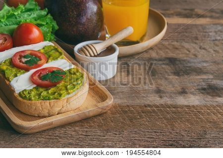 Open sandwich for breakfast or lunch. Sandwich spread with cream cheese avocado and tomato. Avocado and cream cheese open sandwich style serve with orange juice on wood table with copy space. Avocado cream cheese sandwich ready to served.