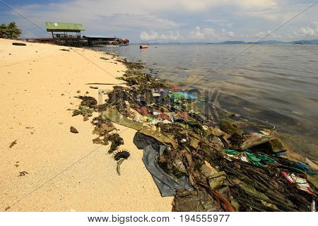 MABUL, MALAYSIA - CIRCA JULY 2017: Plastic pollution environmental proble. Plastic carrier bags, bottles and straws dumped by seaside fishing village