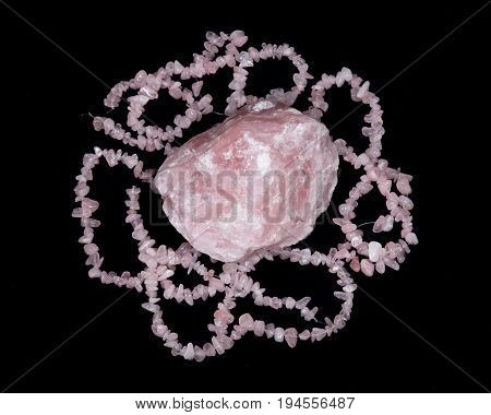 Raw rose quartz from Madagascar and polished rose quartz strings on black background