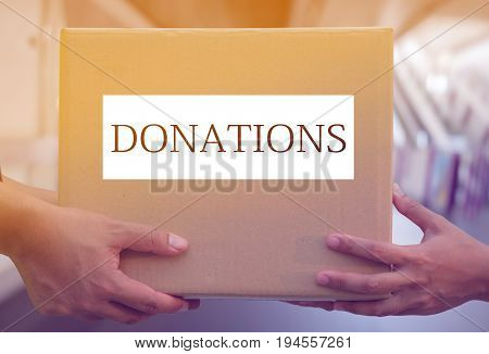 volunteer Hand holding donation box for help.