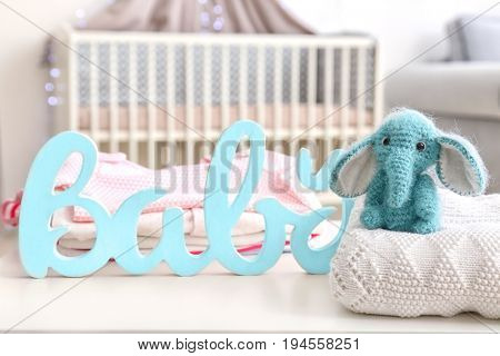 Cute baby elephant with decor on table in bedroom