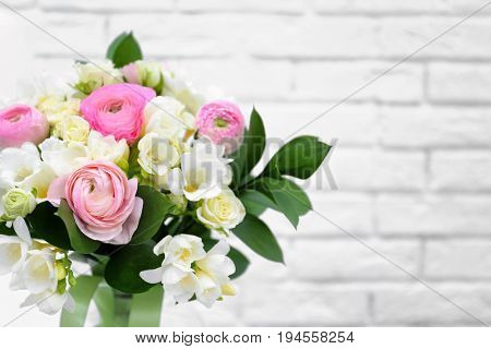 Beautiful bouquet with freesia flowers on white brick wall background