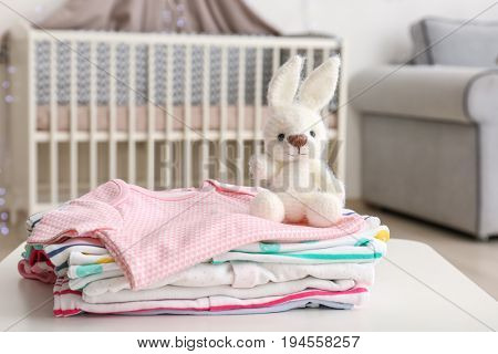 Handmade crochet bunny toy with baby clothes on table in bedroom