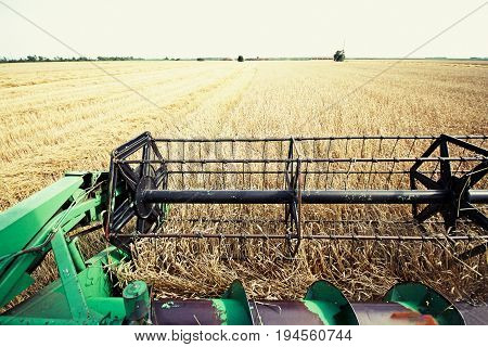 Combine harvester on a wheat field with blue sky