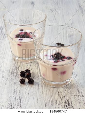 Sour cream in glass with black currants. Sour cream with berries