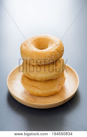 Sugary Donut On A Wooden Plate On A Dark Table Background. In A Morning Light. Breakfast Concept