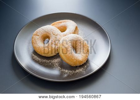 Sugary Donut On A Black Plate On A Dark Table Background. In A Windows Light. Breakfast Concept