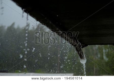 There is a downpour. From the roof of the country house flows water. heavy rain. Natural colors.