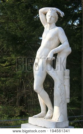 Peterhof, St. Petersburg - May 15, 2010: Statue in antique Greek style - Naked muscular youth (Cupid) in Peterhof, St. Petersburg
