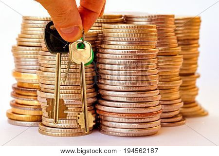 The keys to the apartment in the background the columns of coins . The concept of financial instability on the real estate market .