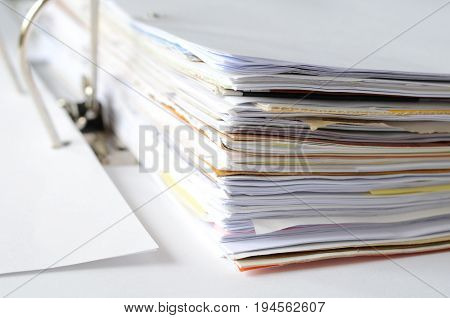 Business documents in document file at workplace, high key tone.