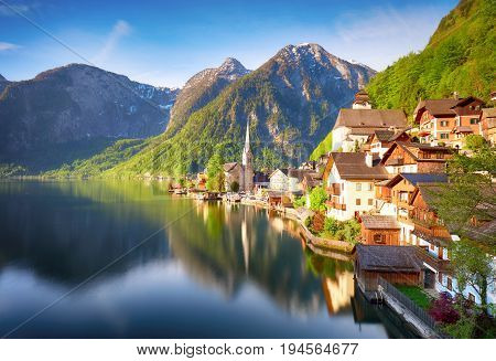 Classic postcard view of famous Hallstatt lakeside town reflecting in Hallstattersee lake in the Austrian Alps in scenic morning light on a beautiful sunny day in summer Salzkammergut region Austria