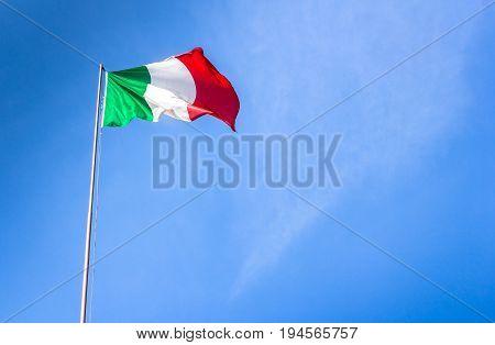 Waving Italian flag tri color against blue sky