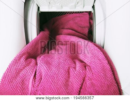 Close Up of pink towel getting out from washing machine
