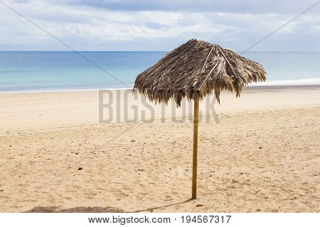Single umbrella on lonely beach. Isolates parasol on Canary zen beach with beautiful sand