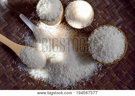 Rice in bowl rice in a spoon rice in a crab jasmine rice is on a wooden floor with light as a background.