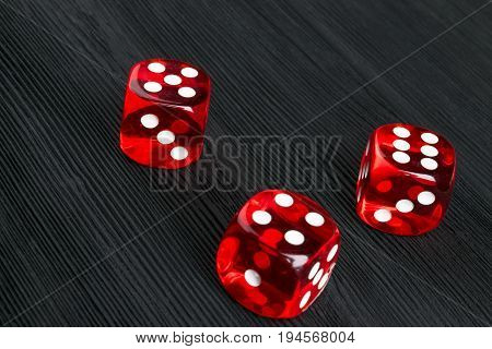 risk concept - playing dice at black wooden background. Playing a game with dice. Red casino dice rolls. Rolling the dice concept for business risk chance good luck or gambling