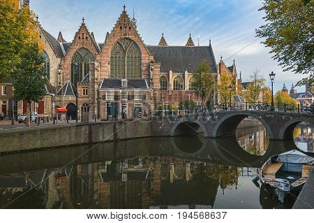 Amsterdam, Netherlands - October 30 2016: The Old Church in the red light district is the oldest building in the city of Amsterdam