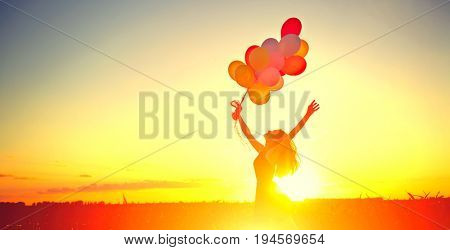 Beauty girl running and jumping on summer field with colorful air balloons over Sunset clear sky. Silhouette, Happy young healthy woman enjoying nature outdoors. Running and jumping female. Flying