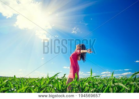 Beauty girl on summer field rising hands over blue clear sky. Happy young healthy woman enjoying nature outdoors. Running and Spinning female. Flying. Free, freedom concept, environment