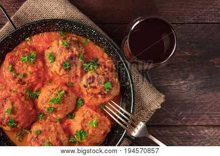 An overhead photo of meatballs in tomato sauce, shot from above in the skillet on dark rustic textures, with a place for text, a fork, and a glass of red wine