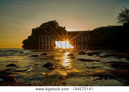 Scenic Sunset And Rays Of Sunlight Shines From Rock Hole At Tanah Lot In Bali Island Indonesia