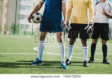 partial view of soccer players and referee standing on soccer pitch before game