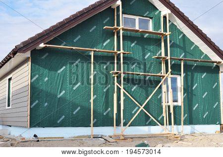 KYIV UKRAINE - JULY 11 2017:   Building Repair Remodeling House with Plastic Siding and Insulation Membrane Mineral Wool.Foundation insulation with styrofoam. Installing Rigid Foam Insulation.