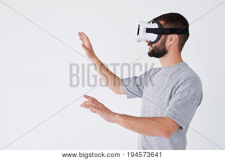 Male playing video game and gesturing with his hands like catching something isolated on white background