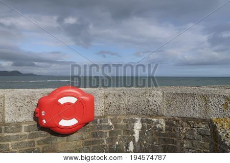 Wall with a lifebuoy case in the corner with the sea and clouded sky on the background