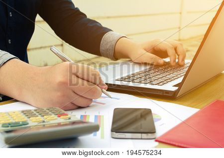 young accountant or business man working and writing with report sheet calculator laptop smartphone finances and calculate on desk savings business economy concept sunlight effect