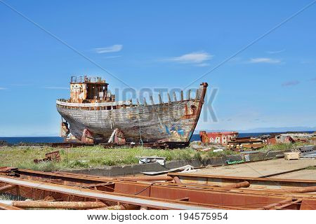 Rusty wooden and metal shipwreck in the Icelandic dry dock in the Akranes town as a symbol of corrosion and decay
