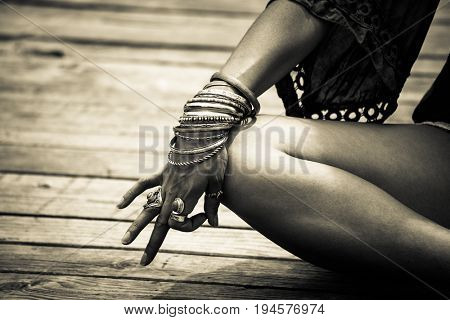 woman hand in yoga symbolic gesture mudra wearing lot of bracelets and rings outdoor closeup summer day bw