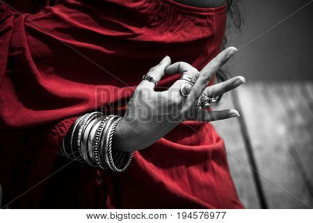woman hand in yoga symbolic gesture mudra wearing red tunic and lot of bracelets and rings outdoor closeup  summer day