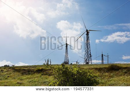 Picture of group of modern windmills for clean energy production. Vast green meadow with windmill turbines producing electrical power. Environment renewable electric energy and technologies